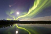 Aurore boréale et pleine lune au-dessus de la rivière — Photo de stock