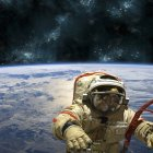 Cosmonaut floating in space above Earth, stars shining on background — Stock Photo