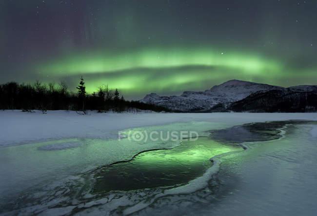 Reflected aurora over frozen Laksa lake — Stock Photo