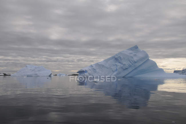 Iceberg and cloudy sky reflected in water — Stock Photo