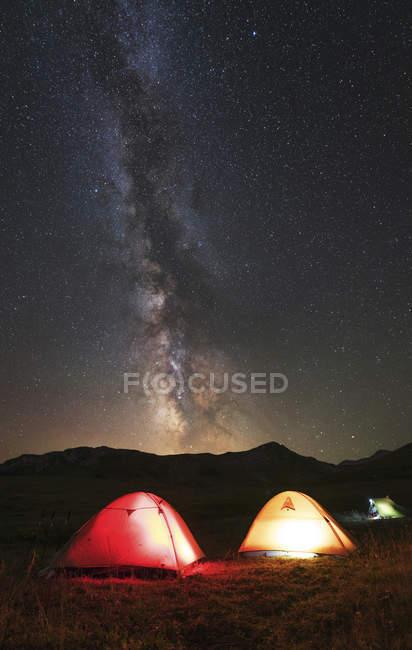 Tiendas que brilla intensamente bajo la vía Láctea - foto de stock