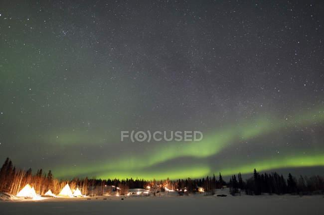 Aurora borealis and Milky Way over village — Stock Photo