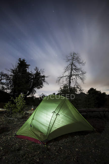Lightened tent under cloudy sky — Stock Photo