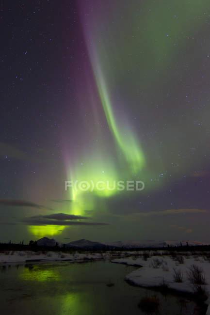 Aurora borealis over creek by Fish lake — Stock Photo
