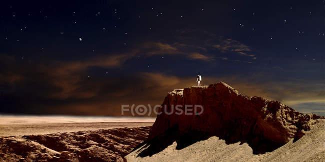 Astronauta em pé na pedra — Fotografia de Stock