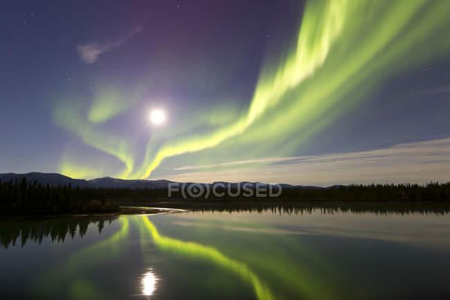 Aurora borealis and full Moon over river — Stock Photo