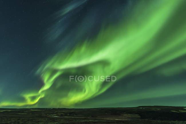 Colorful aurora borealis over night landscape — Stock Photo