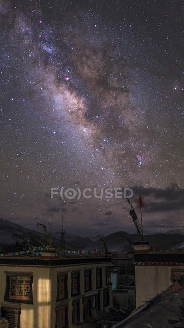 Starscape with Milky Way over village - foto de stock