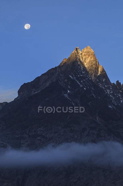 Monduntergang und Alpenglühen über verschneite Gipfel — Stockfoto