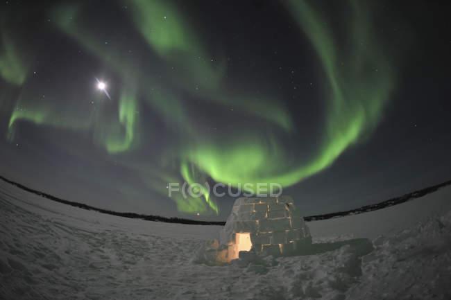 Aurora boreal sobre iglú en el lago Walsh - foto de stock