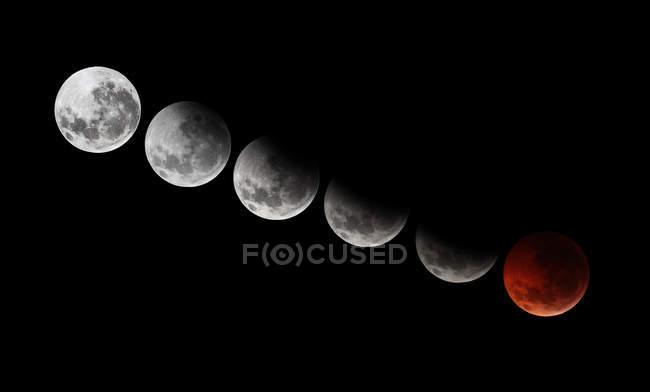 Diferentes etapas de 2010 eclipse total de la luna solsticio sobre fondo negro - foto de stock