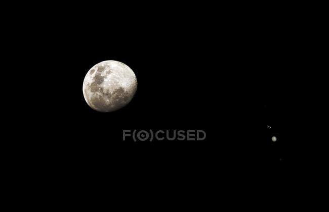 Lune et Jupiter séparées par 6 degrés sur fond noir — Photo de stock