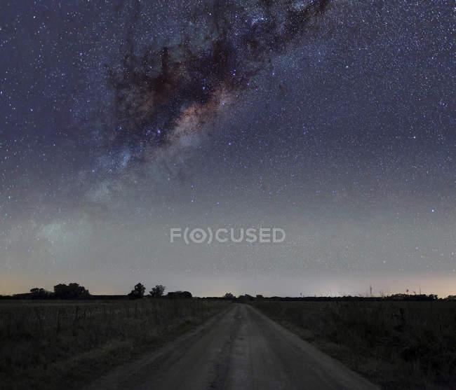 Centro de la Vía Láctea sobre carretera rural en Mercedes, Argentina - foto de stock