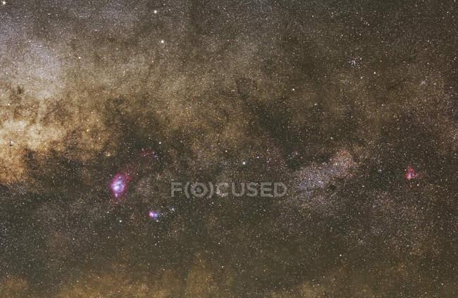 Milky Way from Lagoon Nebula to Omega Nebula including red and blue Trifid nebula — Stock Photo