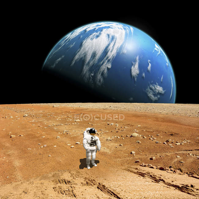 Astronaut looking up at alien sun and standing on barren planet — Stock Photo
