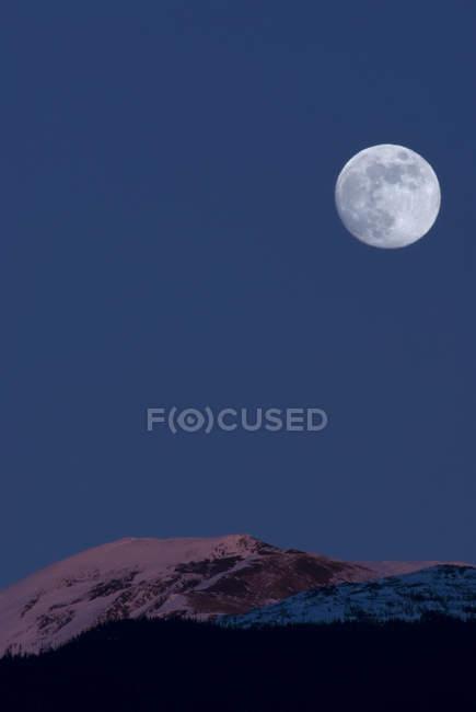 Luna llena sobre montañas en Alpenglow, New Aiyansh, Columbia Británica, Canadá - foto de stock