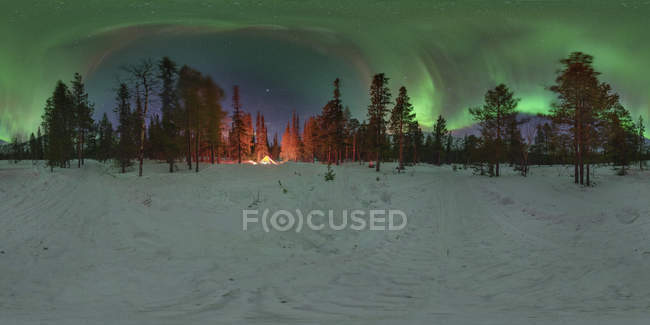 Panorama of aurora over winter forest with glowing tent in Kola Peninsula, Russia — Stock Photo