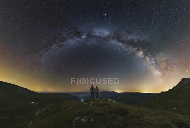 Пара, дивлячись на Чумацький шлях від верхнього Lago НАКи плато з видом, Росія — стокове фото