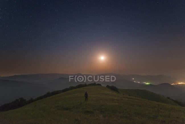 Чоловік, що стоїть на горах вночі під місяцем, Судаку, Крим — стокове фото