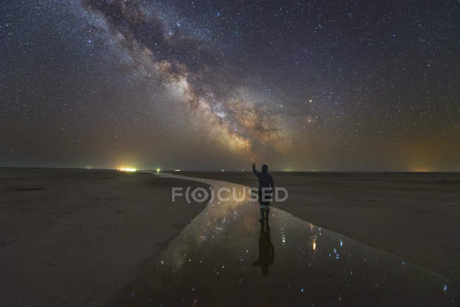 Man walking on salt river at night under Milky Way with stars reflected in river, Russia — Stockfoto