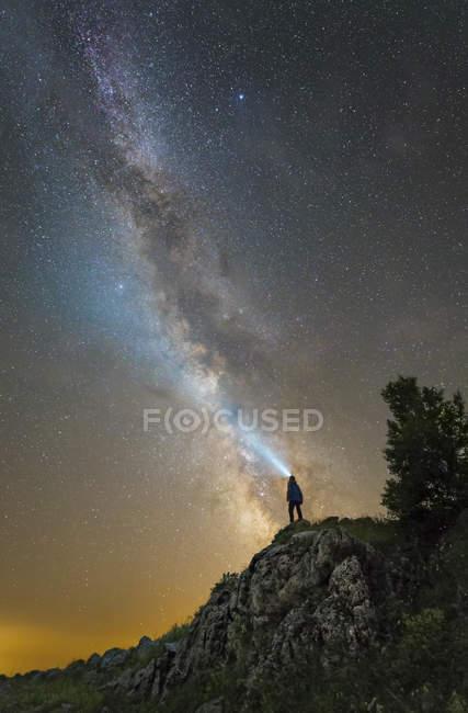 Hombre de pie sobre rocas de la meseta de Lago-Naki y linterna brillante en la Vía Láctea, Rusia - foto de stock