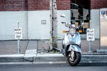 Scenic view of motorbike parked on street — Stock Photo