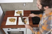 A man prepares dinner plates for three. — Stock Photo