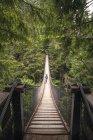 Mann zu Fuß über Lynn Canyon Suspension Bridge in der Nähe von Vancouver, Kanada — Stockfoto