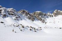 Un esquiador de pista masculino y su piel de perro a través de la nieve fresca en la cuenca de colmena cerca cielo grande, Montana - foto de stock