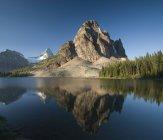 Mount Assiniboine reflected in Sunburst Lake at sunrise — Stock Photo