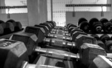Black and white photo of arranged dumbbells in gym — Stock Photo