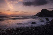 Praia rochosa e turva ondas ao entardecer com farol de Tillamook Rock em distância no Parque Estadual de Ecola, Oregon — Fotografia de Stock