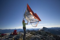 A female backpacker shakes the dirt out of her tent after camping on a rocky mountain ridge in British Columbia, Canada. — Stock Photo