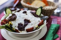 Greek salad with tzatziki on top served in bowl — Stock Photo