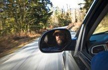 A mans cara reflejada en un espejo de rearview de camiones conduciendo por una carretera en Squamish, British Columbia - foto de stock
