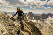 A woman rock climbing the SE ridge of West Twin Peak in Titcomb Basin, Wind River Range, Bridger Teton National Forest, Pinedale, Wyoming. — Stock Photo