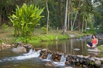 Woman sitting at a waterfall with her laptop by a small pond in northern Thailand — Stock Photo