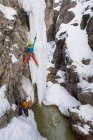 A man and woman ice climbing a frozen waterfall in the Ouray Ice Park, Ouray, Colorado. — Stock Photo