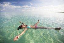 Молода жінка плаває на спині з її кінцівки, витягнув на мілководді бірюзовими на відпочинок острів Коко, Куба. — стокове фото