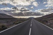 Scenic Empty straight road with mountain and clouds — Stock Photo