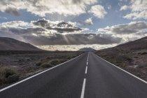 Мальовничі порожній пряма дорога з гори та хмари — стокове фото