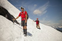 Two climber cross a snowfield high in the mountains of British Columbia, Canada. — Stock Photo