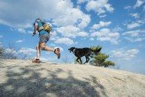 Trail Runner und Hund laufen bis zum Gipfel von Dom Ledge in New Hampshire — Stockfoto