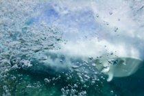 Nahaufnahme der Blase im Wasser nach brechende Welle mit unscharfen Surfbrett auf Hintergrund — Stockfoto