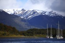 Scenic view of boats at anchor on Beagle Channel in front of picturesque backdrop of Cordillera Darwin mountain range — Stock Photo
