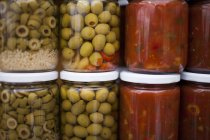 Canned jars of olives and salsa for sale at a local farm market — Stock Photo