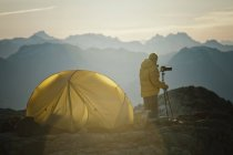 A photographer captures an image using a tripod early in the morning while camping on a rocky mountain ridge in southwest British Columbia, Canada. — Stock Photo