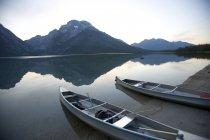 Zwei Kanus in der Abenddämmerung sind am Ufer des Sees Leigh mit den Grand Teton in der Ferne gestrandet. — Stockfoto