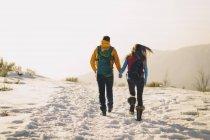 Pareja joven y bebé niño senderismo en las montañas nevadas - foto de stock