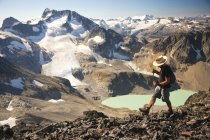 A hiker crosses a rocky ridge near Mount Cook with views of Wedge Mountain and Wedgemount Lake, a part of Garibaldi Provincial Park, seen in the backdrop. — Stock Photo